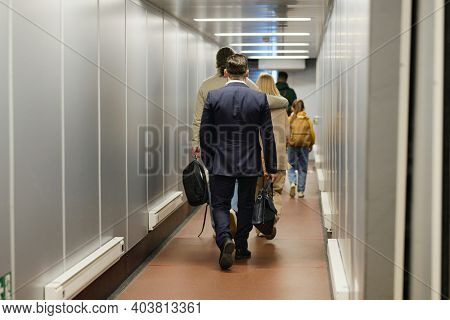Rear view of people going along the corridor of airport terminal for boarding