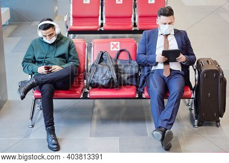 People in protective masks sitting on chairs in the waiting room of the airport and waiting for departure
