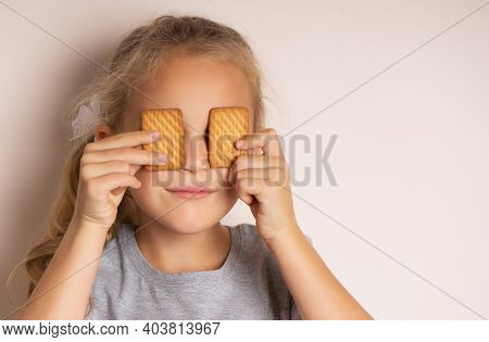 Full Of Sweet Taste. Cute Little Girl Having Fun With Cookies. The Beautiful Girl Covered Her Eyes W