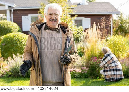 Retired man in eyeglasses and warm jacket holding worktools for gardening against his wife taking care of flowers growing ni the garden