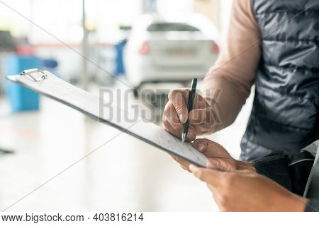 Hand of female technician of automobile repair service holding document while male client with pen putting his signature after repairing car