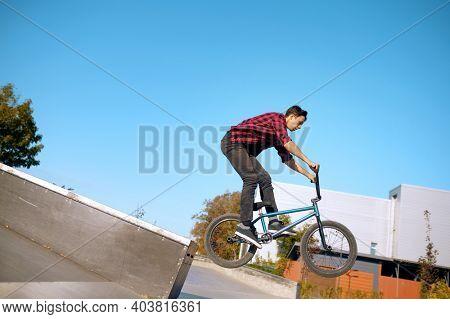 Bmx biker doing trick on stairs in skatepark