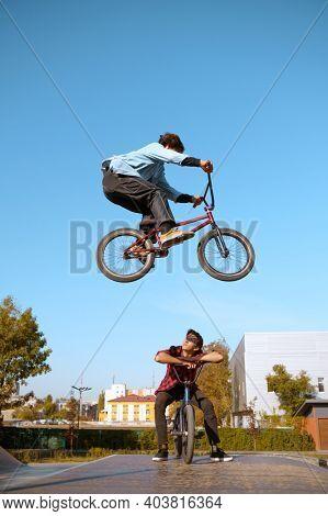 Bmx biker, jump in action, training in skatepark