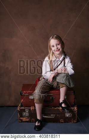 Little Girl Sits On Suitcases. Vintage Style Photography. Child In A White Shirt, Pants And A Hat Wi