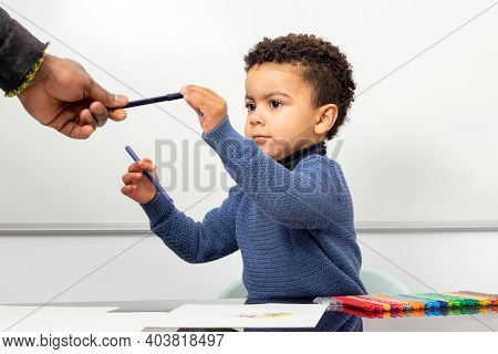 Close Up Portrait Of Teacher Giving Marker Pen To Afro American Kid. Boy Sitting At Table Ready To P