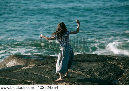 Young dancers woman is engaged in choreography on the ocean coast.