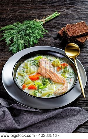 Lohikeitto, Salmon Fish Soup With Cream, Potato, Carrots, Leek And Dill In A Black Bowl On A Dark Wo
