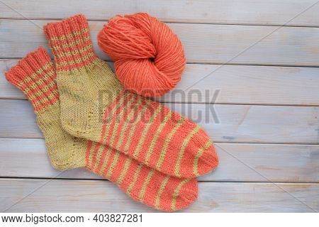 Handmade woolen knitted striped socks on wooden table. Green and orange handmade dyeing yarn