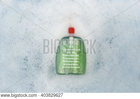 A Bottle Of Liquid Soap Floating In Soapy Water. Harmful Composition Of Ingredients, Detergent With
