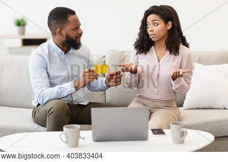 Spender. Angry Black Husband Holding Credit Card, Blaming His Wife For Overspending And Wasting Too