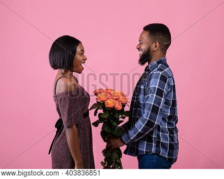 Side View Of Positive Black Man Presenting Flowers To His Girlfriend Over Pink Studio Background. Pa
