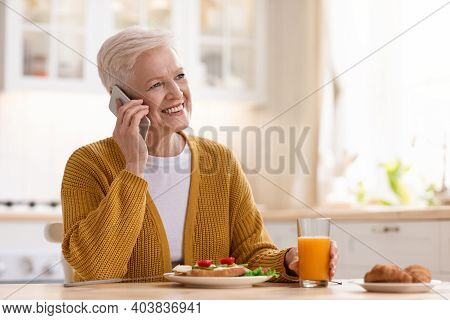 Happy Elderly Woman Having Healthy Lunch And Talking On Mobile Phone, White Kitchen Interior. Smilin