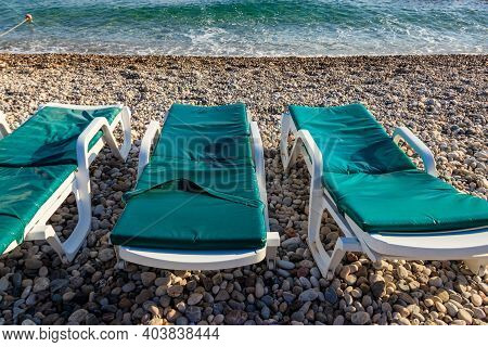Chaise Lounges On A Pebble Beach. Concept Of Rest, Relaxation, Holidays, Resort