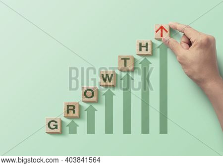Wooden Blocks Arranged In A Staircase With The Word Growth And Increasing Arrows On Green Background