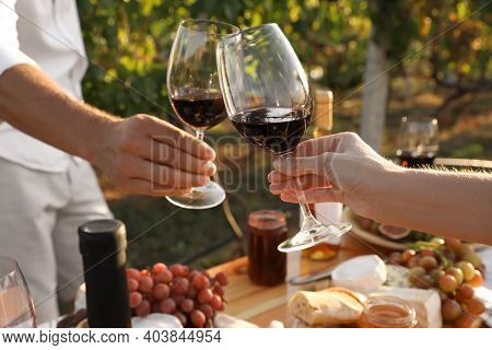 Couple With Glasses Of Wine In Vineyard On Sunny Day, Closeup