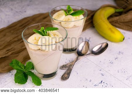 Delicious Banana Mousse With Sliced bananas In Glasses On A White Background.