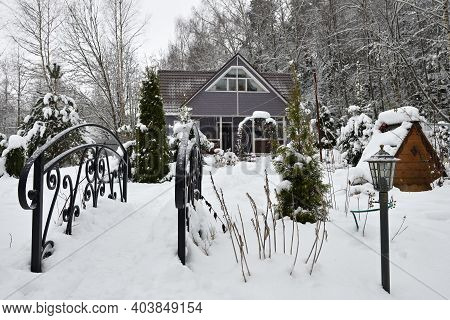 Wooden Country House In Winter, Metal Decorative Bridge And Frozen Trees At Snowfall, Russia