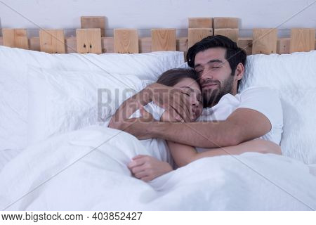 Funny Married Couple Lying In Bed And Hiding Under White Blanket