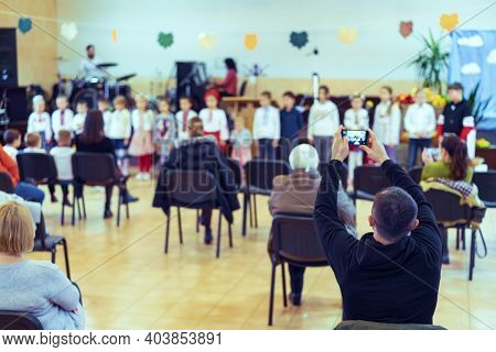 Parents At The Performance Of Children In Kindergarten Or School. Children On Stage. Many Parents Ar