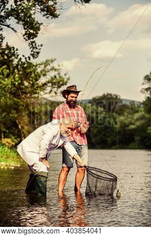 Friends Catching Fish. Hobby And Recreation. Catching Fish With Soulmate. Bearded Man And Brutal Hip
