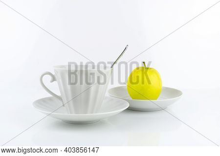 White Porcelain Cup With Spoon And Saucer, Yellow Apple On Saucer, On White Surface