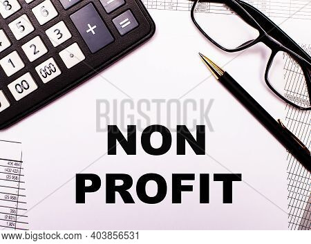 On The Reports There Is A Calculator, Glasses, A Pen And A Notebook With The Inscription Non Profit