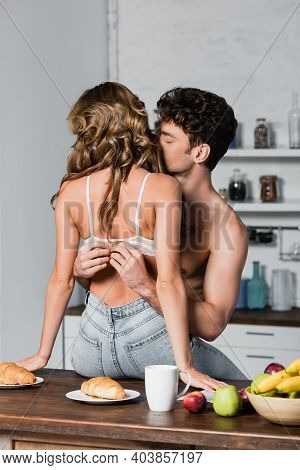 Shirtless Man Taking Off Bra From Sexy Woman Near Breakfast On Table