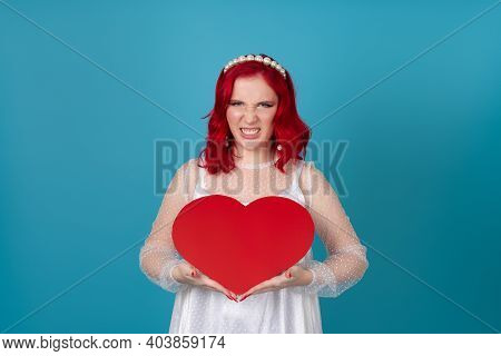A Scandalous, Angry, Frustrated, Predatory Young Woman In A White Dress And With Red Hair Holds A La