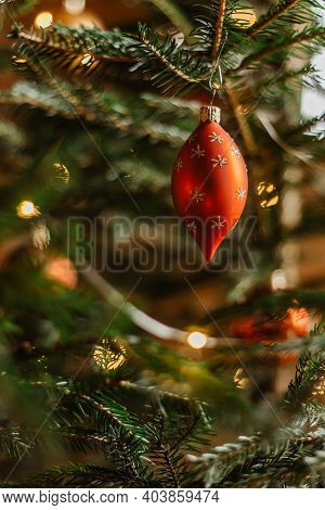 Christmas Tree With Red Shiny Bauble. Festive Xmas Ornament Hanging On Tree Blurred Background.tradi