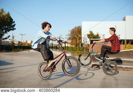 Two male bmx bikers doing tricks in skatepark