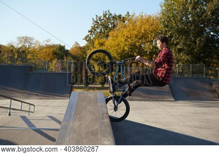 Young male bmx biker jumps on the wall