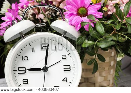 White Alarm Clock Against The Background Of Fresh Flowers In A Wicker Basket. Spring Time.