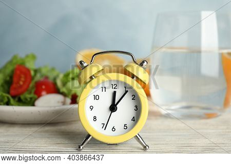 Alarm Clock And Healthy Food On White Wooden Table. Meal Timing Concept
