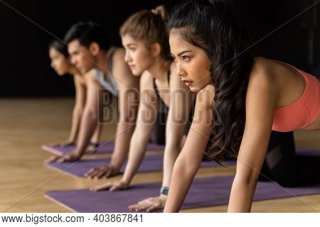 Group Of Asian Women And Man Doing Push-up Exercises On Yoga Mats In Aerobics Class. Young Sporty Pe