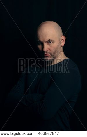 Portrait Of A Brutal Bald Man In A Dark Style On A Black Background. A Bald Athletic Guy In A Black