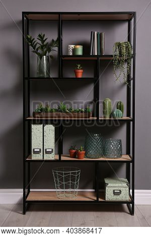 Shelving With Different Decor, Books And Houseplants Near Gray Wall. Interior Design