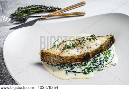 Baked Halibut Fish Steak With Spinach. White Background. Top View