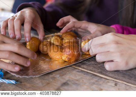 Hands Of Young People Sharing Fritters With Cream On Wooden Table