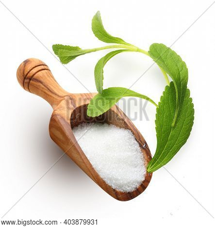 Wooden spoon of white sugar and stevia on wooden background