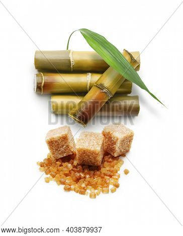 Sugar cube and cane plant isolated on white background.