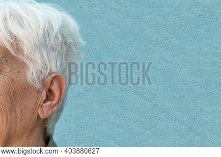 Side View Of An Elderly Womans Head Showing Ear, Gray Hair And Facial Skin With Wrinkles On A Blue B
