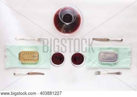 Cans Of Preserves On Green Napkins And Red Wine On White Background, For Lunch Or Dinner At Home By