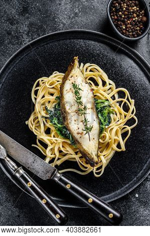 Spaghetti Pasta With Halibut Fish Steak And Spinach. Black Background. Top View