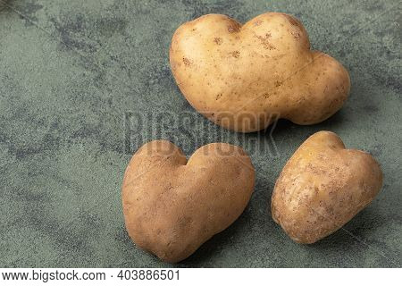 Three Large Potatoes On A Dark Green Background. Funny Abnormal Shape Potatoes.