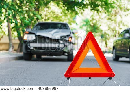 Red Emergency Stop Triangle Sign On Road During A Car Accident. Broken Gray Car In Road Traffic Acci