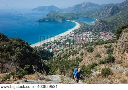 Hiking on Lycian way. Man with backpack is trekking steep part in mountains with view of Oludeniz beach and Blue Lagoon from Lycian Way trail, Mediterranean coast in Turkey