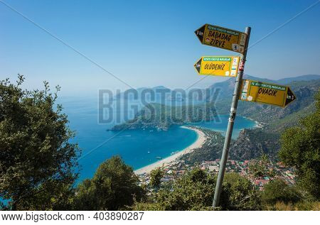 Oludeniz, Turkey - 1 October, 2019: Lycian Way direction yellow signpost pointing with view of Oludeniz beach and Blue Lagoon, Mediterranean coast
