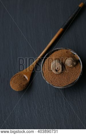 Nutmeg.whole And Grated Nutmeg In A Black Cup And Wooden Spoon On A Black Slate Background. And Herb