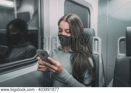 Public transport commute woman commuter at night wearing face mask riding subway using mobile phone. Asian passenger with face coronavirus covering on train commute ride.