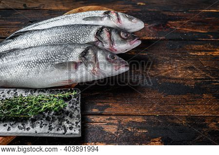 Fresh Raw Fish Seabass On A Cutting Board. Dark Wooden Background. Top View. Copy Space